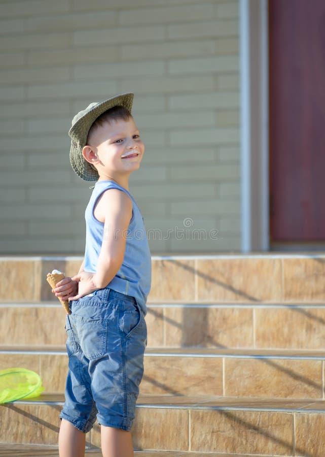 De jonge Kegel van het Jongens Verbergende Roomijs achter Rug stock afbeeldingen