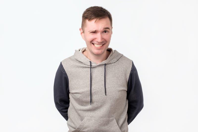 De jonge kerel die hebbend vrolijk ziet grijnzen eruit stock foto