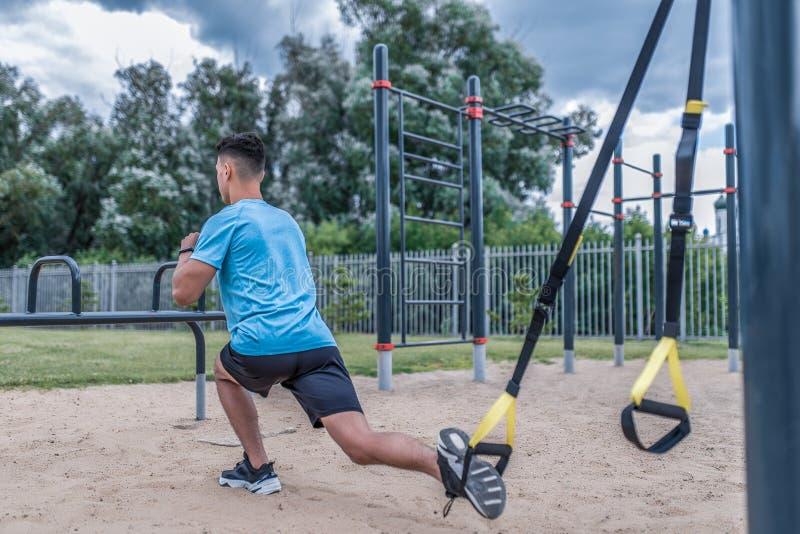 De jonge kerel het mannelijke atleet doen blik van rug uitvalt, hurkt de sportengrond van de stadszomer, singelbandlijnen, beensp stock foto