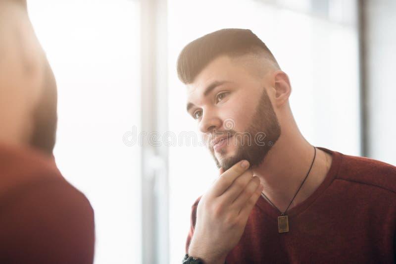 De jonge kerel kijkt in de spiegel stock afbeeldingen