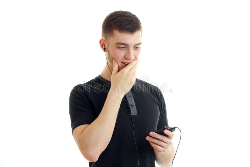 De jonge kerel luistert aan muziek met hoofdtelefoons en sluit de mondhand stock foto