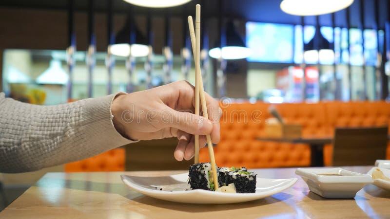 De jonge kerel met eetstokjes neemt sushi van een plaat in een Japans restaurant royalty-vrije stock afbeeldingen