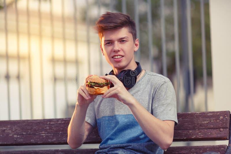 De jonge kerel rust en eet een hamburger bij zonsondergang stock foto's