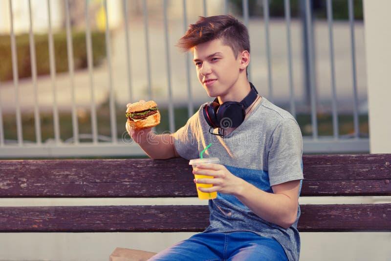 De jonge kerel rust en eet een hamburger bij zonsondergang stock fotografie