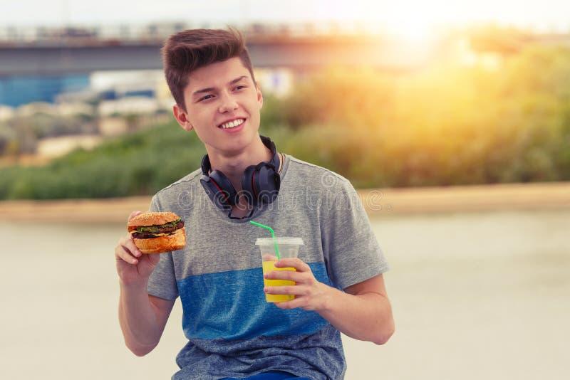 De jonge kerel rust en eet een hamburger bij zonsondergang stock afbeeldingen