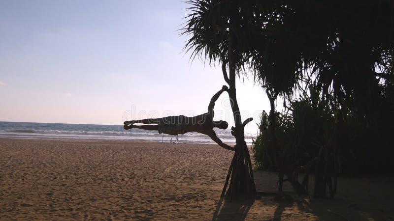 De jonge kerel toont menselijk vlag op zee strand aan Atletische mens die gymnastiekelementen op palm doen bij exotische oceaan stock afbeelding