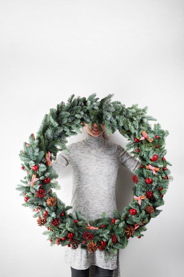 De jonge Kerstmis grote kroon van de vrouwenholding dient binnen lichte, seizoengebonden vakantie, rustiek thema, versiering in royalty-vrije stock afbeelding