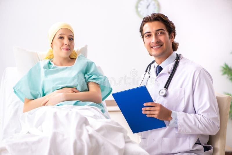 De jonge knappe arts die vrouwelijke oncologiepatiënt bezoeken royalty-vrije stock afbeeldingen
