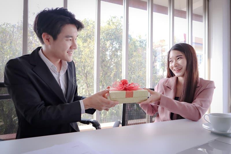 De jonge knappe Aziatische bedrijfsmens biedt gift met glimlach en gelukkig gezicht aan royalty-vrije stock afbeeldingen