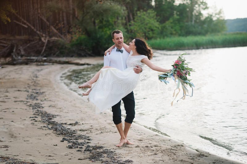 De jonge knappe bruidegom houdt zijn bruid in zijn wapens op het strand met een groot boeket van mooie bloemen royalty-vrije stock afbeelding
