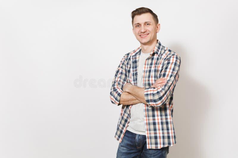 De jonge knappe gelukkige glimlachende mens in grijze t-shirt, jeans, de geruite handen van de overhemdsholding kruiste over bors stock foto