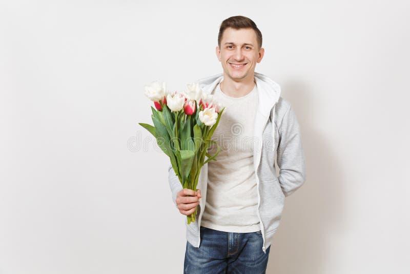 De jonge knappe gelukkige glimlachende mensenstudent in t-shirt en licht sweatshirt houdt helder boeket van witte en roze tulpen royalty-vrije stock afbeelding