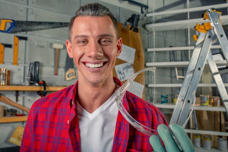 De jonge knappe glimlachende Kaukasische timmerman houdt de veiligheidsbril in van hem zijn workshop indient stock afbeelding
