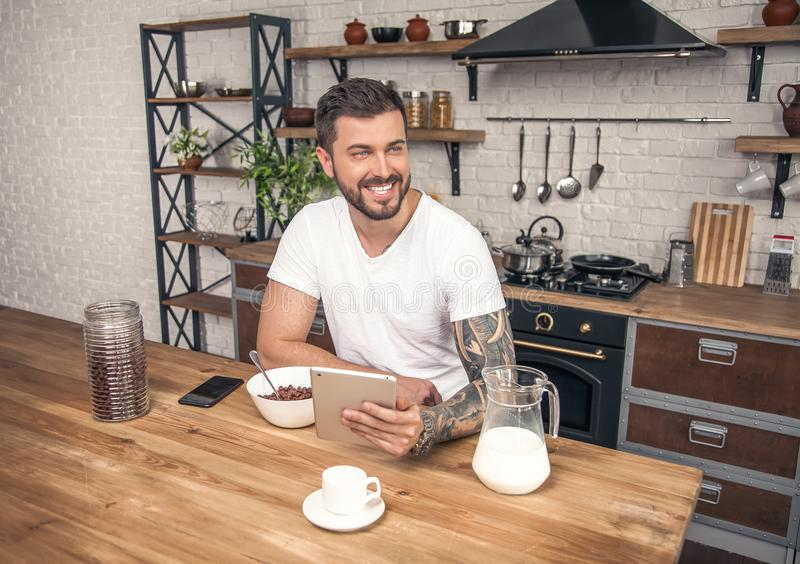 De jonge knappe glimlachende mens heeft zijn ontbijtgraangewassen met melk bij de keuken en leest ochtendnieuws op de tablet royalty-vrije stock foto's