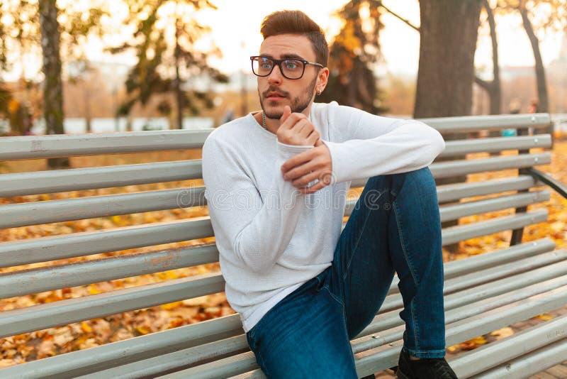 De jonge knappe hipsterkerel zit in de herfstpark op een bank Alleen Bored Een student loopt in het park royalty-vrije stock fotografie
