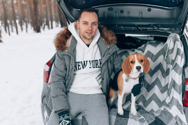 De jonge knappe kerel in een sneeuw de winterbos zit in de boomstam van zijn auto in een greep met zijn het rassenhond van de vri royalty-vrije stock foto