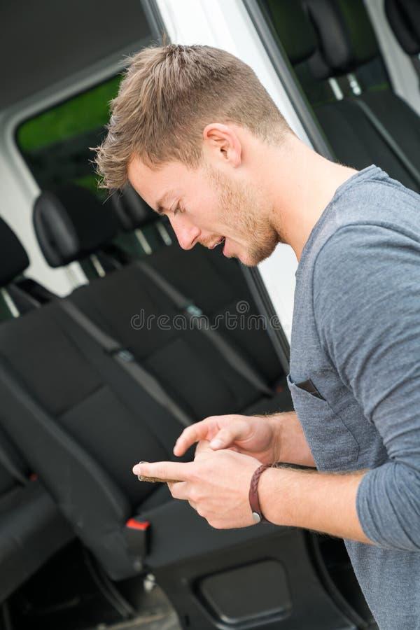 De jonge knappe mens bekijkt zijn mobiele telefoon buiten zijn auto stock foto's