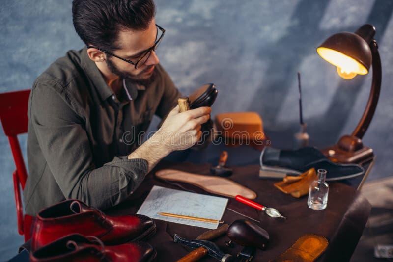 De jonge knappe mens die schoenmakershulpmiddel behandelen, sluit omhoog beeld stock fotografie