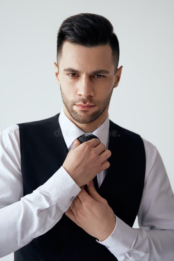 De jonge knappe mens in elegant kostuum past zijn stropdas aan stock foto