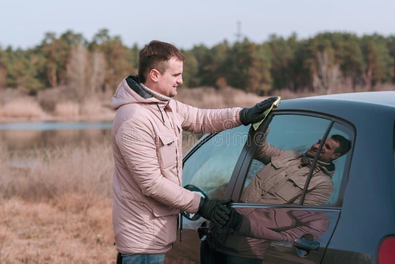 De jonge knappe mens maakt zijn auto met vod schoon alvorens te drijven stock afbeelding