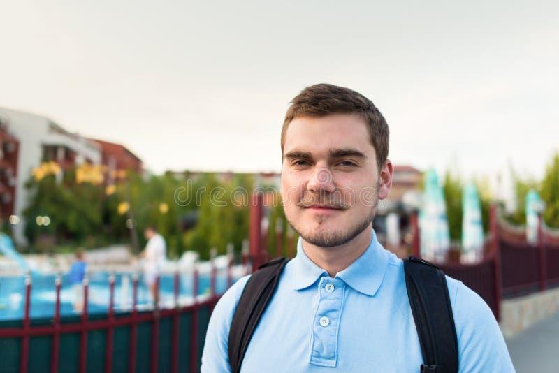 De jonge knappe mens met snor bevindt zich dichtbij complexe flats stock fotografie