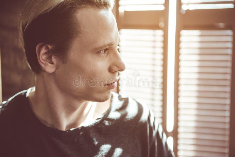 De jonge knappe mens stelt dichtbij venster stock fotografie