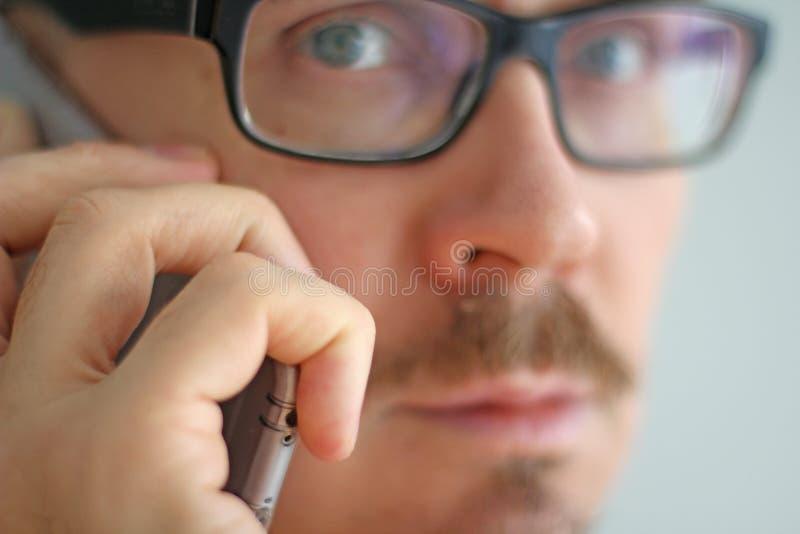 De jonge knappe mens in zwarte glazen spreekt op de telefoon Het portret van de close-up van een mens Manager, beambte, die op sp royalty-vrije stock foto's