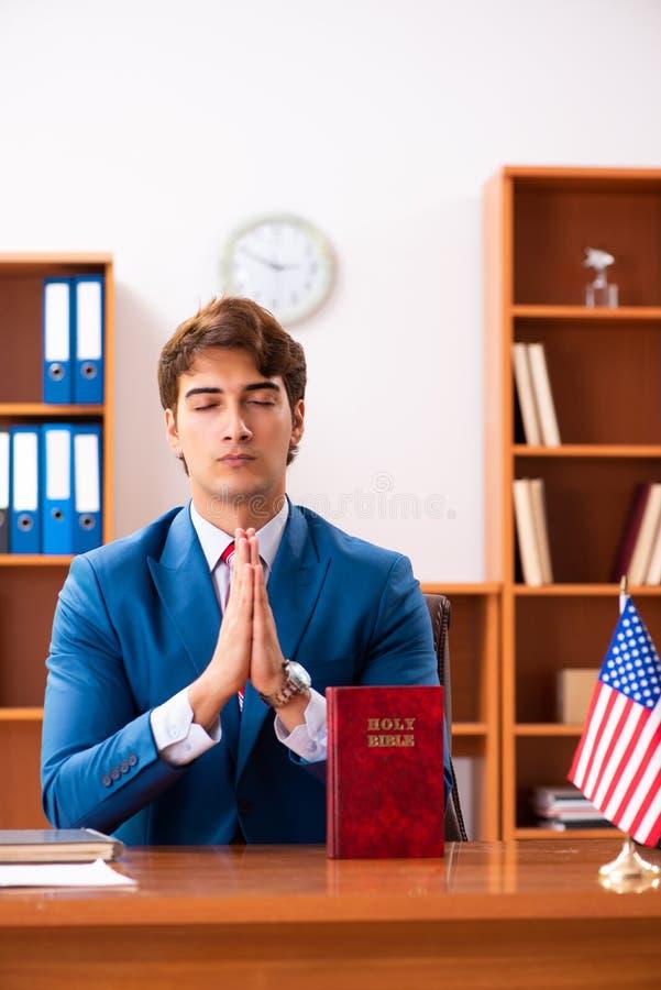 De jonge knappe politicuszitting in bureau stock afbeelding