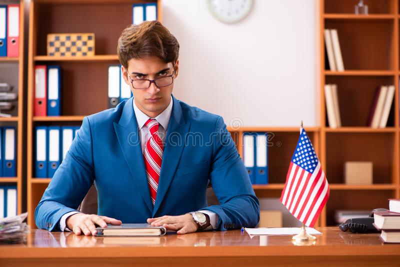 De jonge knappe politicuszitting in bureau royalty-vrije stock foto