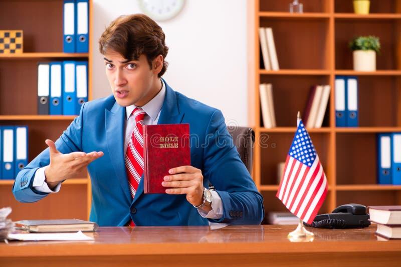 De jonge knappe politicuszitting in bureau royalty-vrije stock fotografie