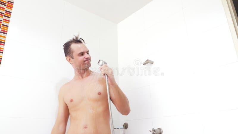 De jonge knappe spiermens neemt een douche de kerel wast, zingt en danst in de douche stock fotografie