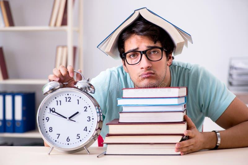 De jonge knappe student die voor schoolexamens voorbereidingen treffen stock foto