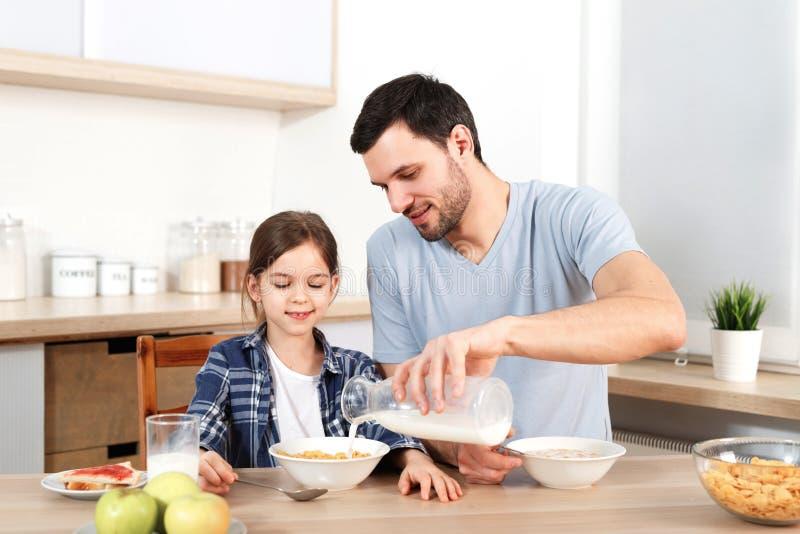 De jonge knappe vader giet melk in kom met vlokken, voorbereidt ontbijt voor klein kind, zit samen bij keuken, heeft stock foto