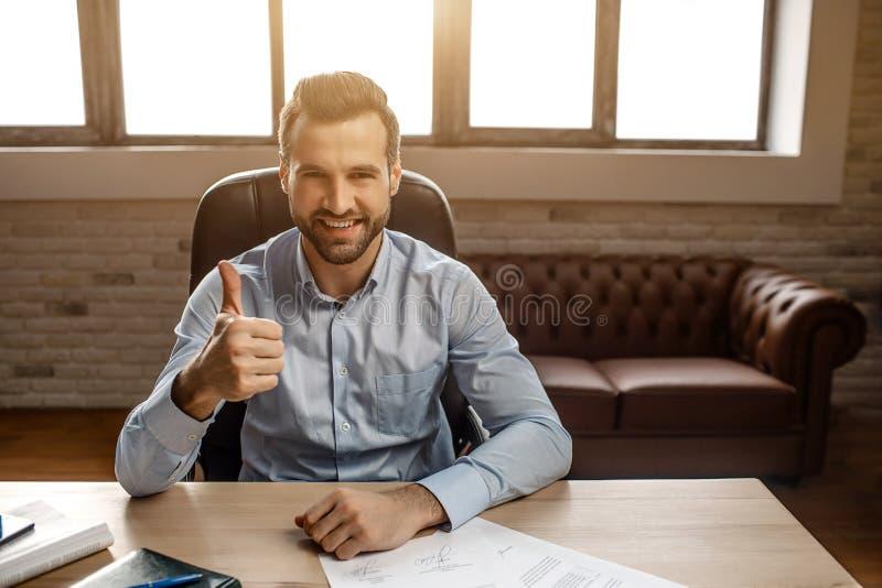 De jonge knappe vrolijke zakenman zit op lijst en stelt in zijn eigen bureau Hij houdt grote duim en glimlach tegen Gelukkig Nice royalty-vrije stock fotografie