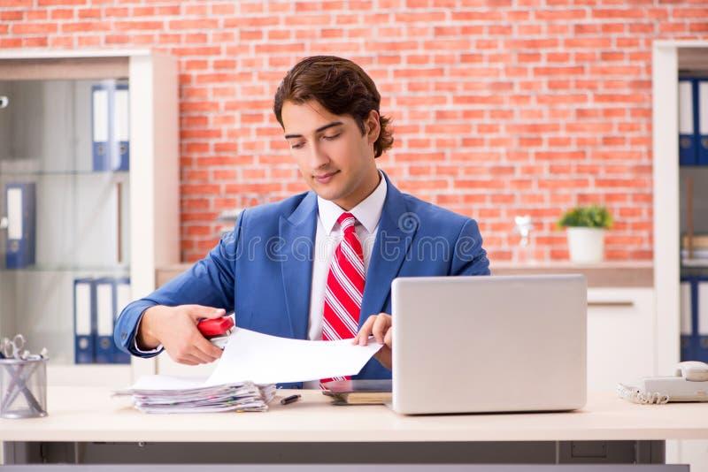 De jonge knappe werknemer die in het bureau werken stock foto's