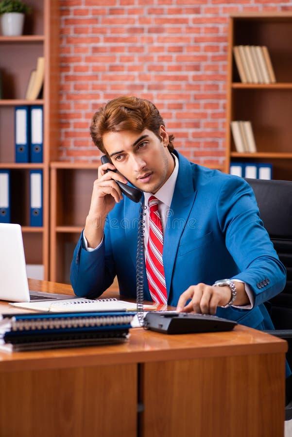 De jonge knappe werknemerszitting in het bureau royalty-vrije stock foto