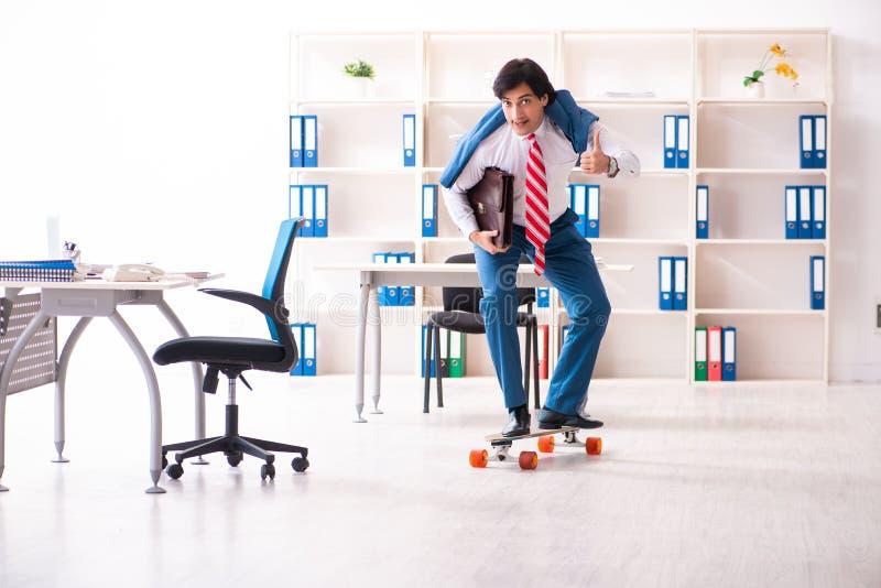 De jonge knappe zakenman met longboard in het bureau royalty-vrije stock foto