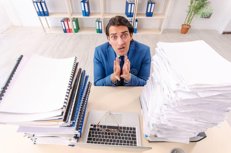 De jonge knappe zakenman ongelukkig met het bovenmatige werk stock afbeelding