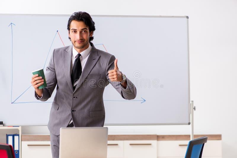 De jonge knappe zakenman voor whiteboard stock afbeeldingen