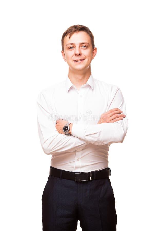 De jonge knappe zakenman in wit overhemd bevindt en kruist zich rechtstreeks zijn handen, portret dat op wit wordt geïsoleerd royalty-vrije stock foto's