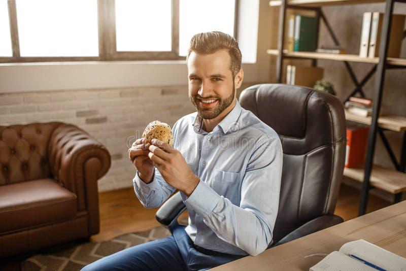De jonge knappe zakenman zit op stoel en heeft lunchtijd in zijn eigen bureau Hij houdt hamburger en glimlach aan camera royalty-vrije stock afbeelding