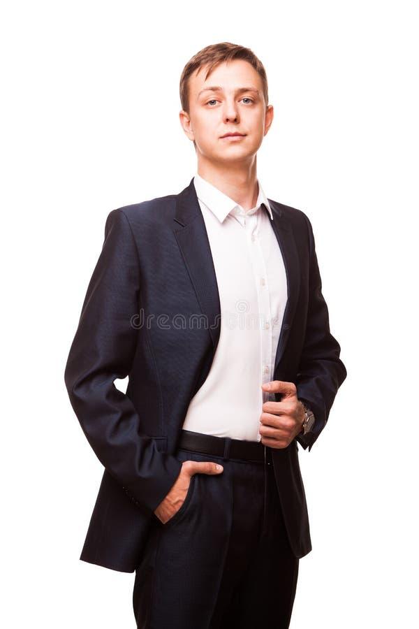 De jonge knappe zakenman in zwart kostuum bevindt zich rechtstreeks en het zetten van van hem dient zakken, geïsoleerd in portret stock fotografie