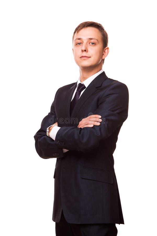 De jonge knappe zakenman in zwart kostuum bevindt zich rechtstreeks met gekruiste wapens, volledig die lengteportret op wit wordt royalty-vrije stock afbeelding