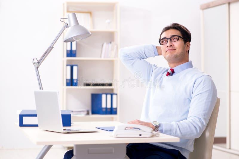 De jonge knappe zakenmanwerknemer die in bureau bij bureau werken stock foto's