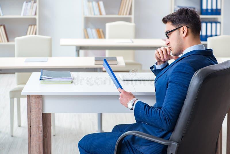 De jonge knappe zakenmanwerknemer die in bureau bij bureau werken royalty-vrije stock afbeelding