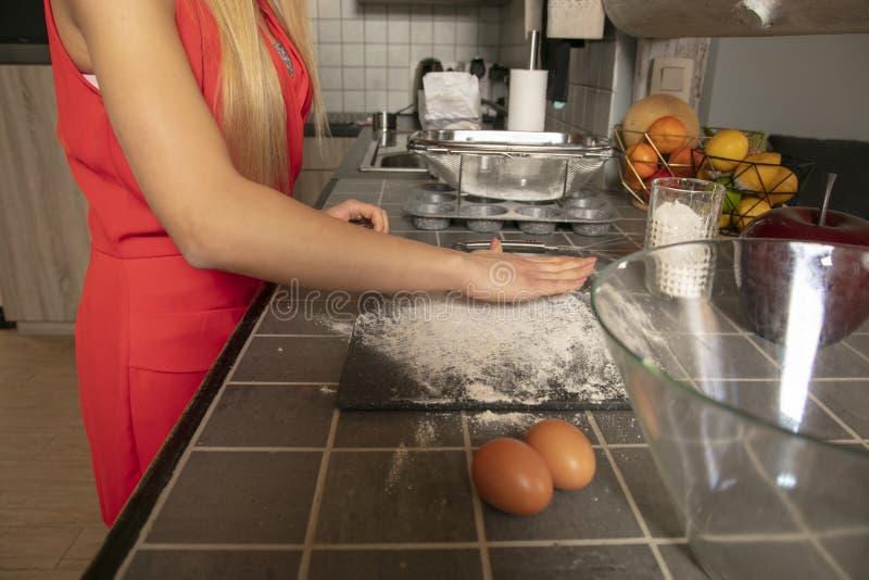 De jonge kok in Kerstmiskleren bereidt iets in de keuken voor, omhoog sluit stock fotografie
