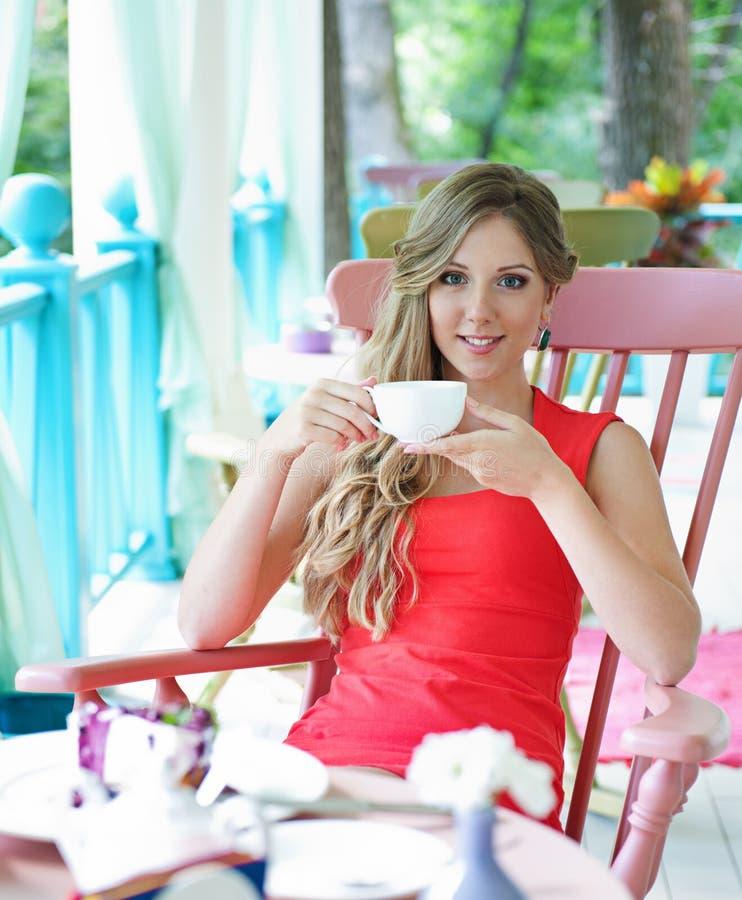 De jonge kop thee van de vrouwenholding stock foto's