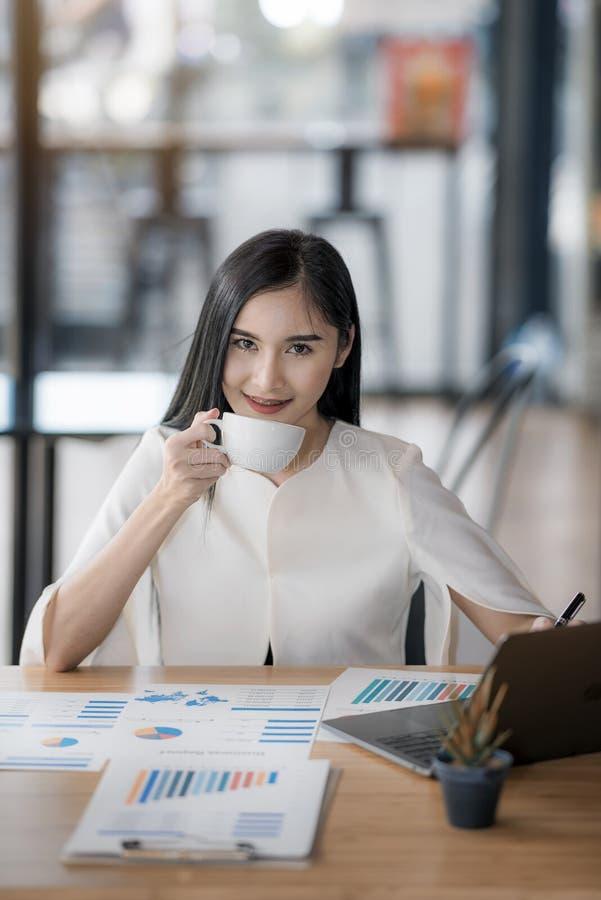 De jonge kop van de bedrijfs Aziatische vrouwenholding van koffie stock afbeeldingen