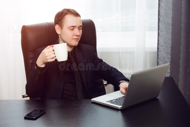 De jonge kop van de zakenmanholding van koffie terwijl het werken aan laptop stock foto