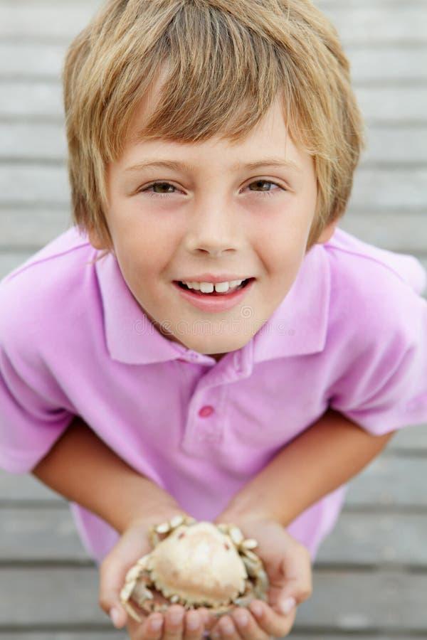 De jonge krab van de jongensholding op strand royalty-vrije stock afbeeldingen